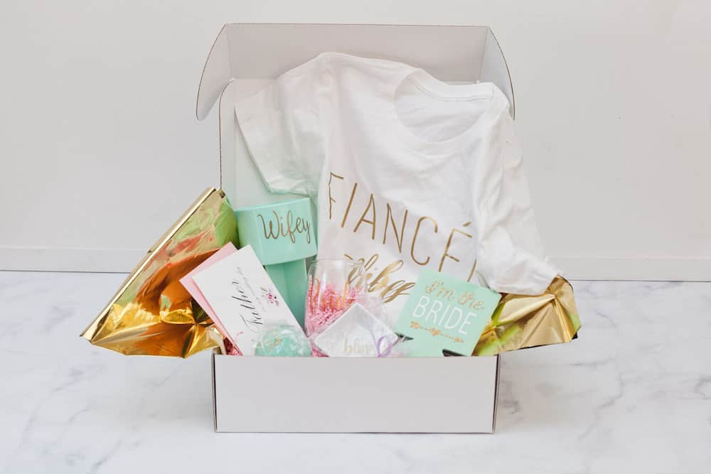 Open box with selection of bridal gifts including white t-shirt with fiancé